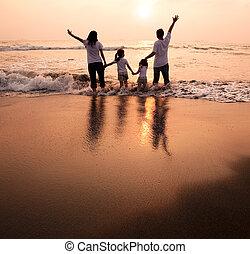 famille heureuse, tenant mains, sur, plage, et, regarder coucher soleil