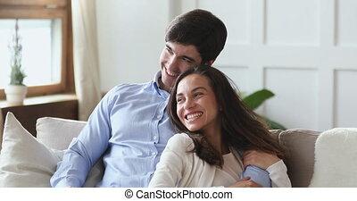 famille, sofa, jeune, couple heureux, étreindre, buts, rêver