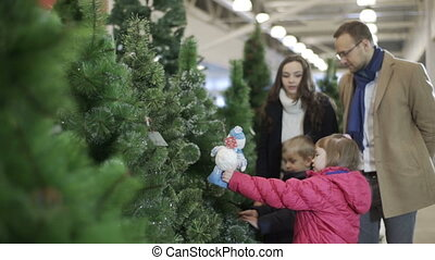 Familly buying Christmas tree at shopping centre. Dolly shot...