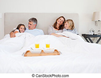 Family about to have breakfast in bed
