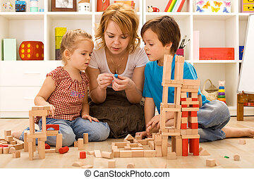 Family activities in the kids room - woman and children ...