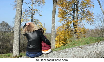 family admire autumn - Blond woman mother sit on cut tree...