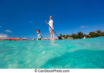 Family adventure holidays - Mother and son paddle boarding...