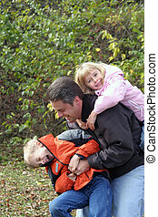 Family Affair - Father playing with son and daughter outside