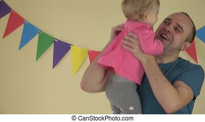 Family affairs - father with baby daughter in arms dancing at party