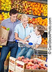 Family against shelves of fruits goes shopping