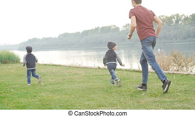 Family and children concept. Happy Father and two sons having fun in summer park