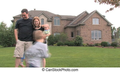 Family of five in front of a large house