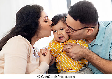happy mother and father kissing baby son at home