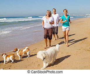 family and pets jogging on beach
