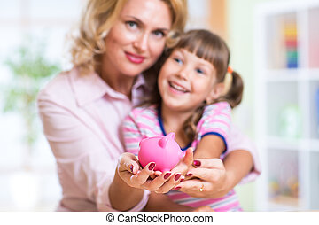 family and savings concept - happy mother and child putting money to piggy bank