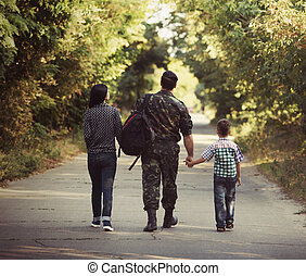 Family and soldier in a military uniform say goodbye before...