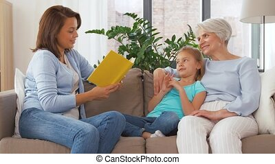 mother, daughter and grandmother reading book - family and...