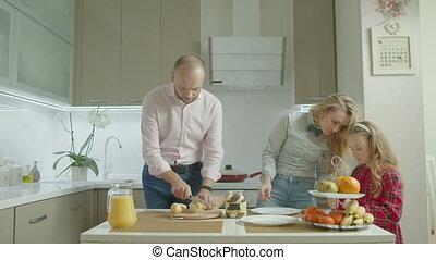 Family applying peanut butter on toast in kitchen - Positive...
