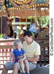 family at amusement park - family of young father and his...