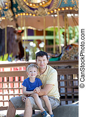 family at amusement park - happy smiling son and his...