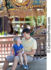 family at amusement park - happy laughing family of two at...