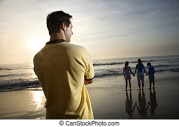 Family at beach. - Caucasian mid-adult man standing and...