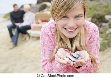 Family at beach with picnic smiling focus on girl with seashells