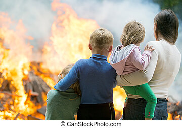 Family at burning house background - Family mother with...