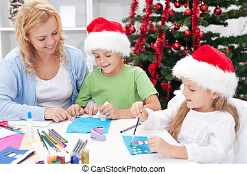 Family at christmas time making greeting cards