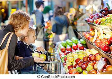 family at farmers market - mother and her son buying fruits...