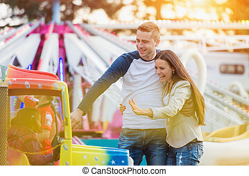 Family at fun fair - Beautiful young family enjoying their...