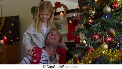 Front view of a middle aged Caucasian man with his young daughter sitting on his shoulders decorating the Christmas tree in their sitting room