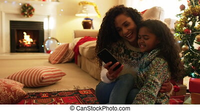 Front view of a mixed race mother sitting on a floor with her young daughter in their sitting room at christmas, taking selfies and looking at a smartphone together