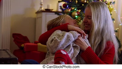 Front view of a young Caucasian woman embracing and tickling her young daughter on her knee in their sitting room at Christmas time, sitting beside a decorated Christmas tree, smiling at each other
