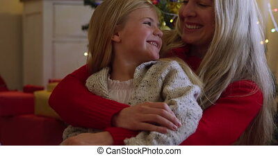 Front view of a young Caucasian woman embracing her young daughter on her knee in their sitting room at Christmas time, sitting beside a decorated Christmas tree, smiling at each other