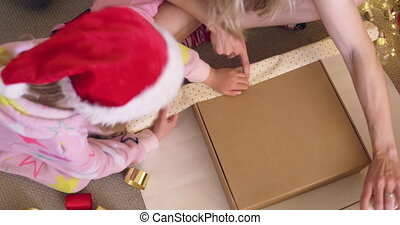 Overhead view of a young Caucasian girl wearing a Santa hat and a onesie wrapping presents sitting on the floor with her mother in their sitting room at Christmas time