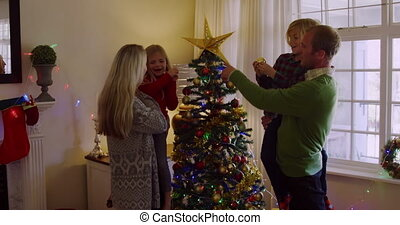 Side view of a Caucasian couple holding their young son and daughter and decorating the Christmas tree together in their sitting room at Christmas time