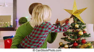 Side view of a middle aged Caucasian man holding his young son and decorating the Christmas tree with him in their sitting room at Christmas time