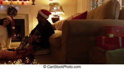 Side view of a mixed race family sitting on the floor with their young daughter in their sitting room at christmas, wearing santa hats, smiling, with dad playing guitar and singing, and the girl playing with fairy lights