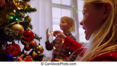 Side view of a young Caucasian bother and sister decorating the Christmas tree in their sitting room at Christmas time