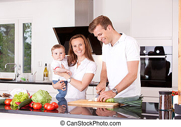 Happy family at home in the kitchen cooking, making a meal