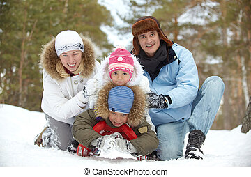 Family at leisure - Happy kids and their parents tobogganing...