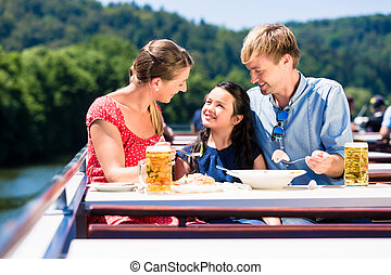 Family at lunch on river cruise with beer glasses on deck