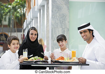 Family at restaurant eating and smiling (selective focus)