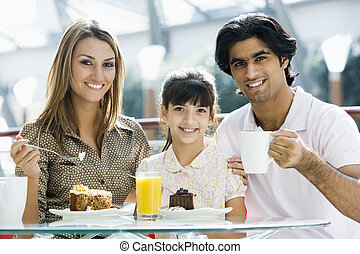 Family at restaurant eating dessert and smiling (selective focus)