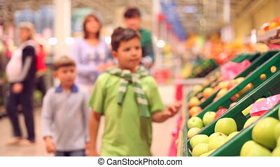 Family at shop - Two boys taking oranges from the shelf and...