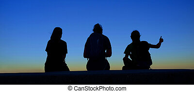 Family at Sunrise or Sunset Sitting Together