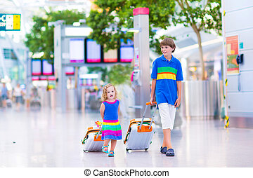 Family at the airport - Two children traveling by airplane...