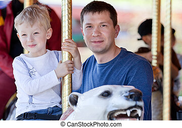 family at the amusement park - excited little boy riding a...