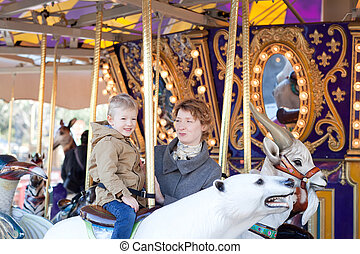family at the amusement park - adorable little boy riding...