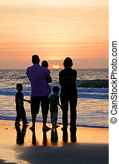 A family of five at the sea in the early morning sunrise.