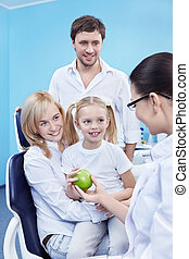 Family at the stomatologist - Dentist gives Apple a child in...