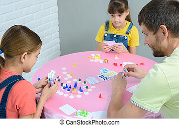 Family at the table plays card board games.