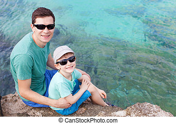family of two sitting at the rocky shore at cayman islands